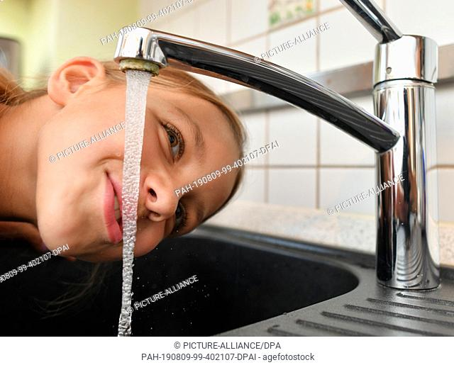 08 August 2019, Brandenburg, Sieversdorf: A girl is drinking tap water from a tap in the kitchen at home. Photo: Patrick Pleul/dpa-Zentralbild/ZB