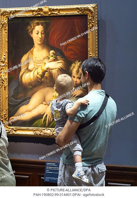 """02 August 2019, Saxony, Dresden: A visitor looks at a picture in the exhibition """"""""Glanzlichter der Gemäldegalerie Alte Meister"""""""" in Semperbau"""