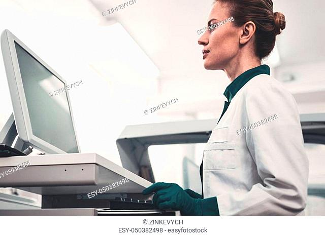 Dedicated to work. Profile of concentrated skilled doctor using hospital computer and expressing interest to work