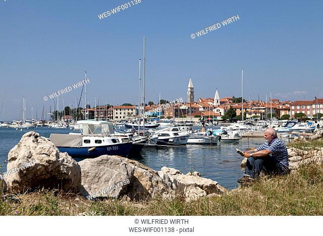 Slovenia, Istria, Izola, man at seashore with marina reading book