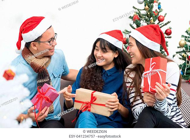 Group of asia friends sitting on sofa celebrate christmas and new year party with gift exchange at decorate tree,gift giving holiday concept