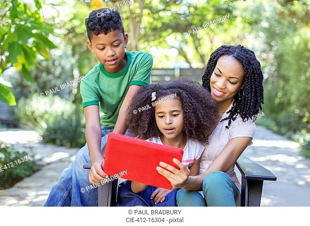 Mother and children using digital tablet outdoors