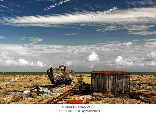 England, Kent, Dungeness. An abandoned wooden boat beached next to a fishermans wooden hut on the shingle beach at Dungeness