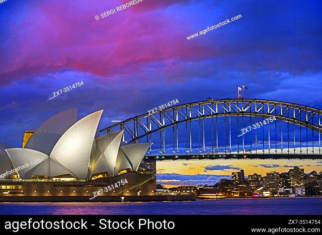 World famous Sydney Opera House and Harbour bridge at sunset. Blurred clouds and lights of landmarks reflect in blurred waters of Harbour