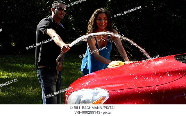Couple wash car at home hispanic couple outside in sun red car fun together love Model Released, MR-12, MR-15