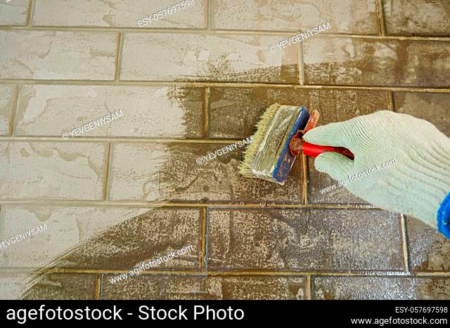 A construction worker applies paint to a brick wall.The painter paints primers the walls with a brush, makes repairs in the house or room