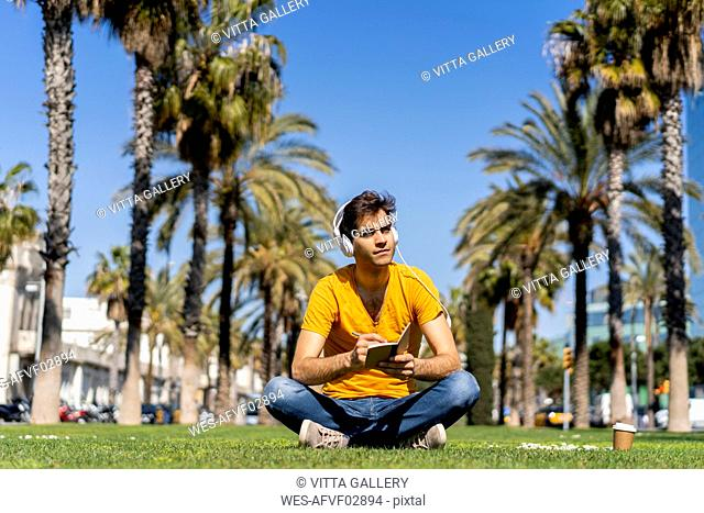 Spain, Barcelona, man sitting on lawn in the city with headphones and notebook