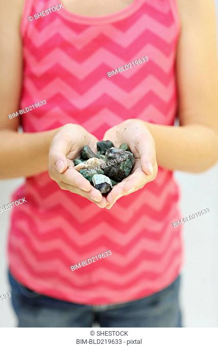 Close up of girl holding handful of stones