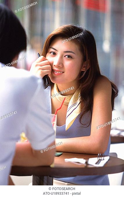 Image of a Young Adult Woman Having a Drink With a Man, Looking at Camera, Smiling, Front View, Rear View, Differential Focus
