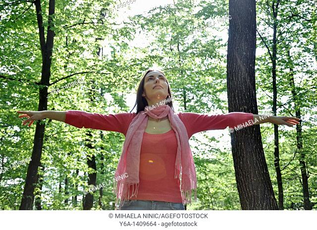 Young woman with outstretched arms in woods