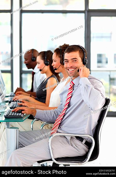 Young businessman in a call center smiling at the camera