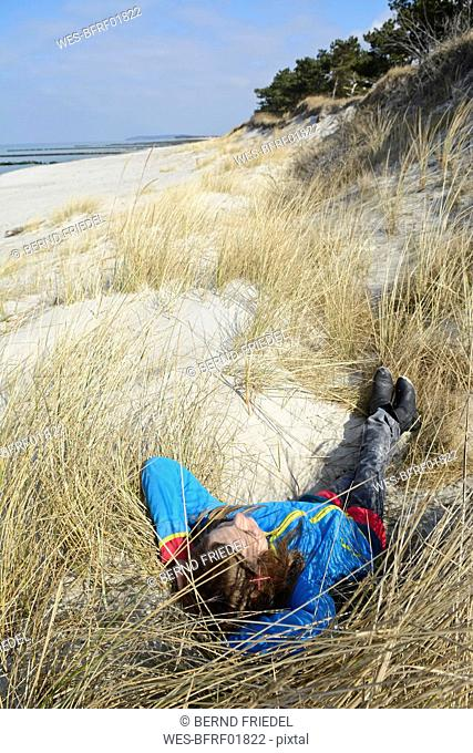 Germany, Hiddensee, girl relaxing in the dunes
