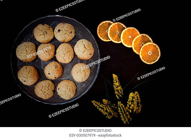 Top view of orange chocolate chips cookies on cake stand, over black background with yellow flowers and orange slices