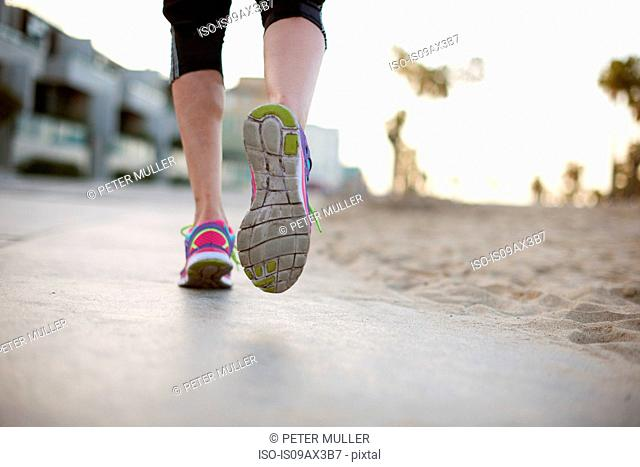 Low section rear view of woman jogging wearing training