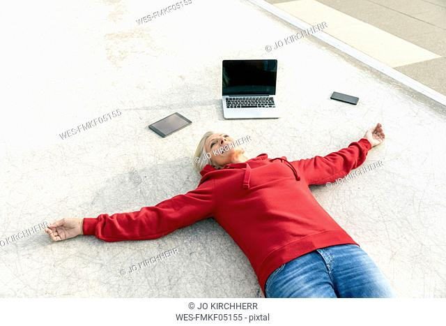 Senior woman wearing red hoodie lying on the ground next to mobile devices