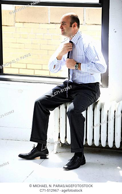 Businessman sitting on radiator fixing tie