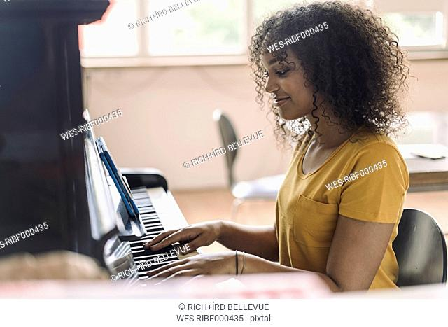 Young woman playing piano, reading notes from digital tablet