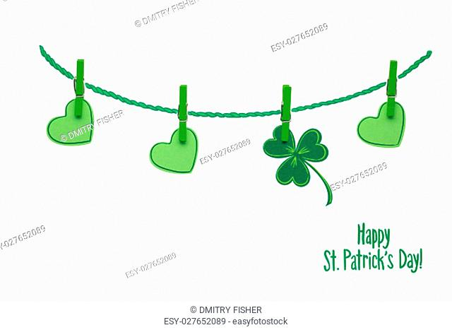Creative St. Patricks Day concept photo of pinned shamrocks and hearts made of paper on white background