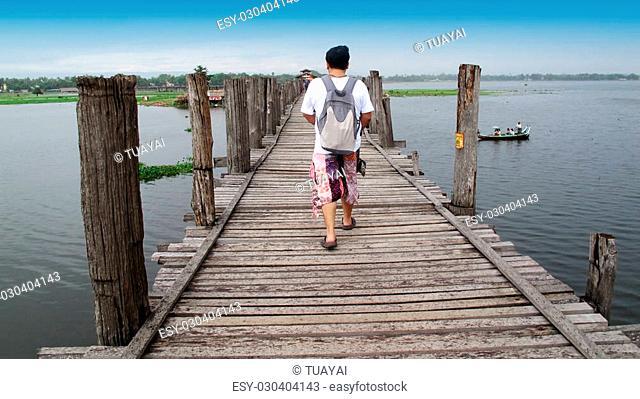 Thai man travel and walking at U Bein Bridge in Amarapura, Myanmar