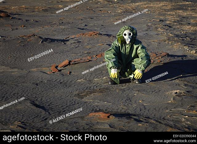 Man in protective clothing sitting in desert