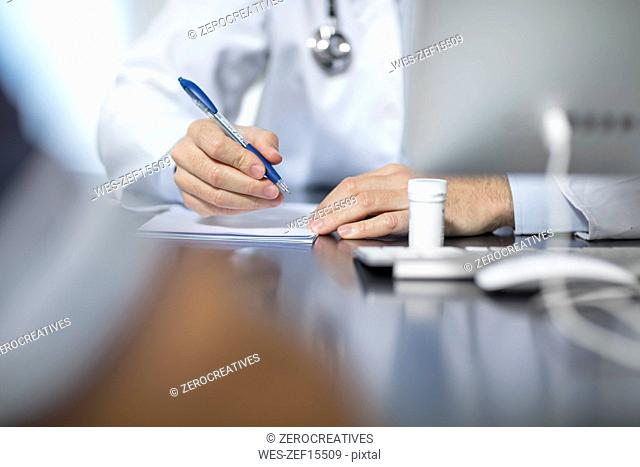 Doctor sitting at his desk taking notes