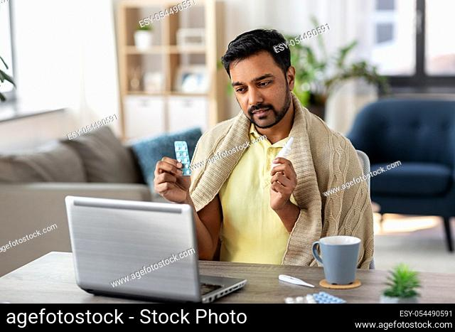 sick man thermometer having video call on laptop
