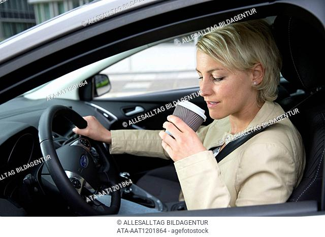 Female car driver is drinking a coffee