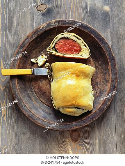 Ox fillet in brioche crust on wooden plate