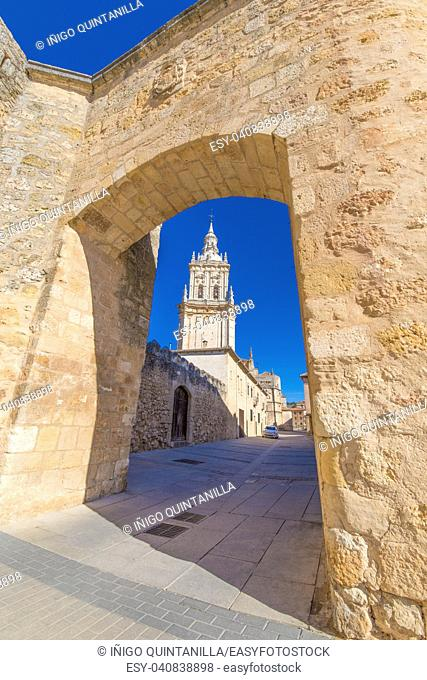 tower of cathedral of Burgo de Osma medieval town through the wall gate arch, public street, landmark and monument from thirteenth century, in Soria, Spain