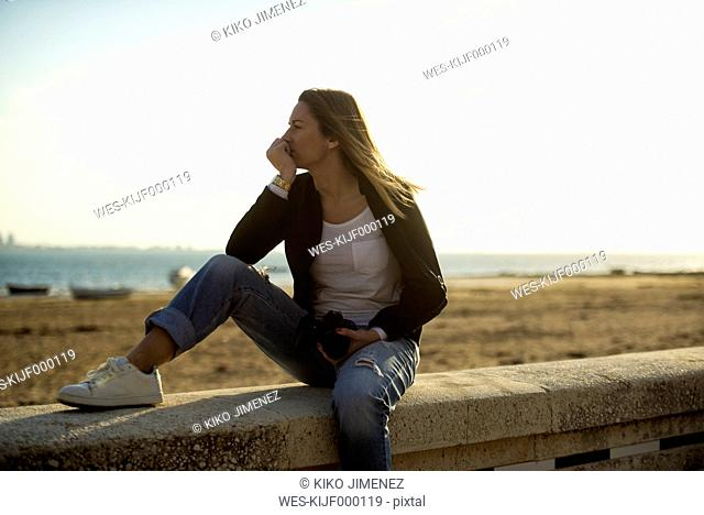 Spain, Puerto Real, woman relaxing on a wall in front of the beach