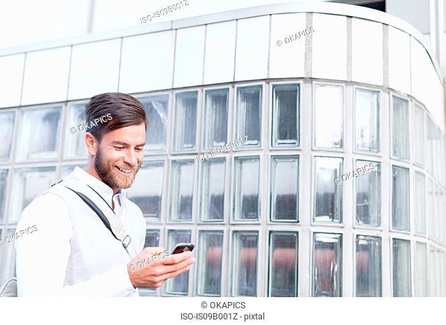 Mature man walking outdoors, using smartphone