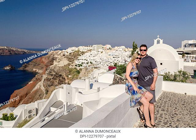 A couple posing together on a white wall on a greek island with the town in the background; Santorini, Greece