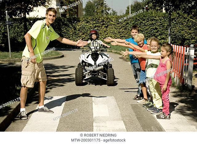 Tutor and children at zebra crossing