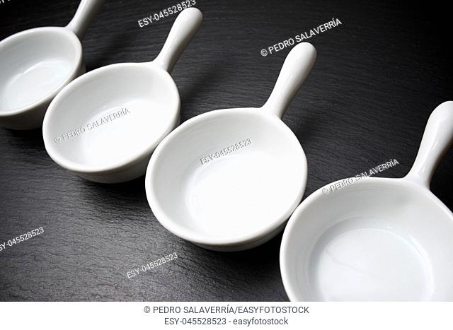 four small white spoons on a table slate