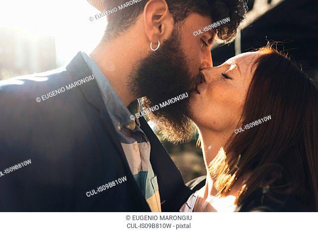 Cool couple kissing on sunlit street