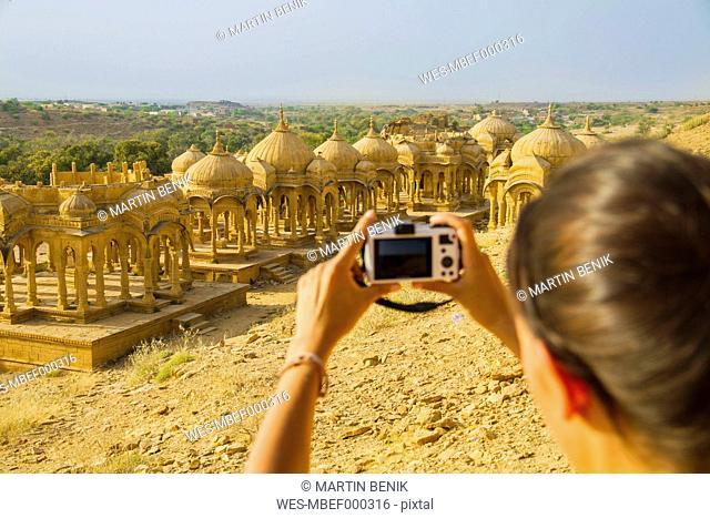 India, Rajasthan,Jaisalmer, Female tourist photographing at Bada Bagh Cenotaphs