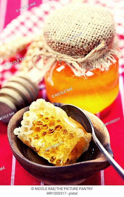 Beautiful honey comb, spoon and honey in jar