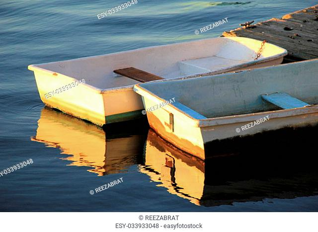 Two old,well used rowboats tied to old wood dock, under early morning sunshine