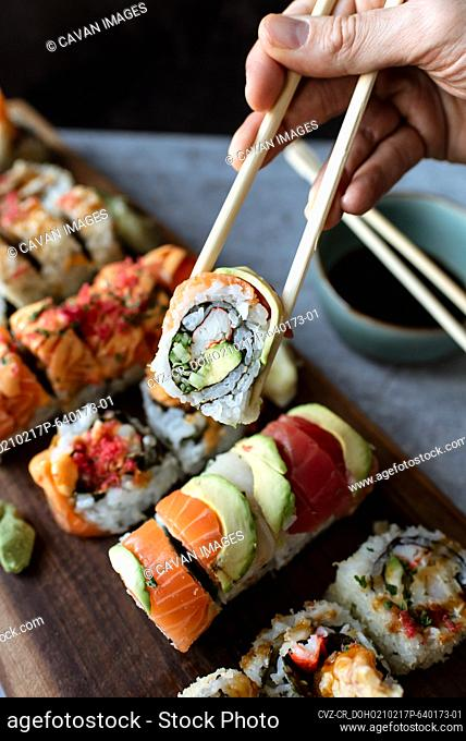 Close up of hand holding sushi roll using chopsticks above a platter