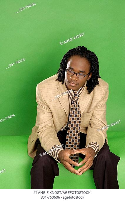 This stock photo shows a fashionable black businessman wearing a suit and sitting casually  Solid green / chroma background includes room for copy