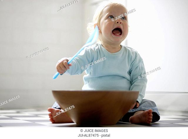 Baby playing with spoon and bowl