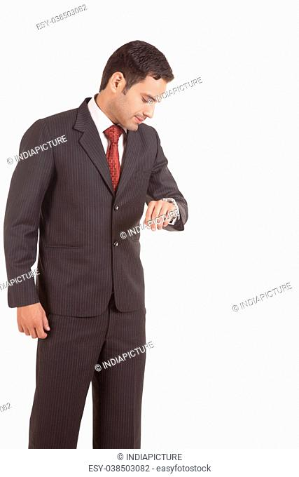 businessman looking at his watch against white background