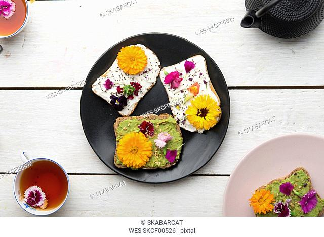 Toast with avocado hummus and sprad cheese with edible flowers