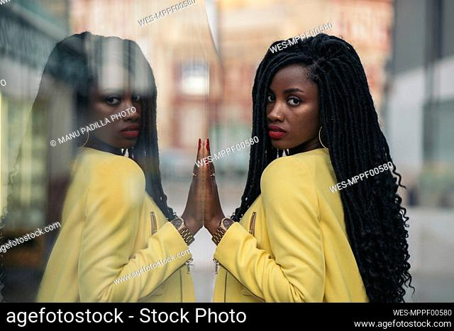 Young woman wearing yellow blazer, mirrored in a window pane