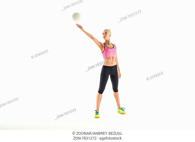 Rhythmic gymnast doing exercise with ball in studio