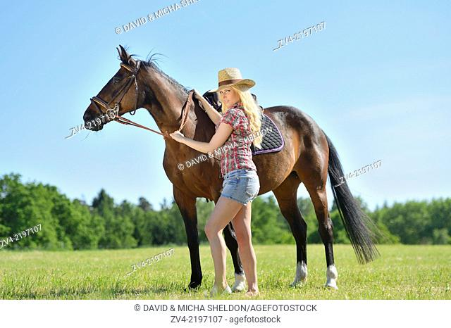 Young cowgirl with a polish arabian horse standing on a meadow