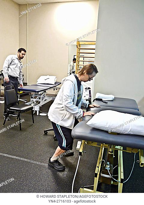A mature woman exercises as her physical therapist looks on