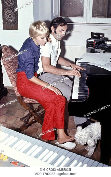 Armenian-born French singer-songwriter Charles Aznavour plays a theme at the piano; beside him sits his third wife, Swedish Ulla Thorsell