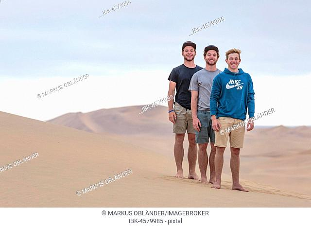 Three young men on sand dune, Namib Desert, Namibia