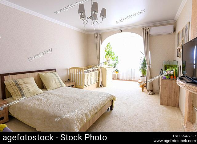 Nice interior of a bedroom combined with a balcony and a crib for a newborn baby